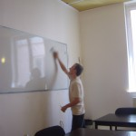 student writing on a whiteboard during a class